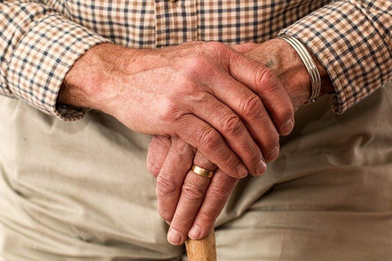 Elderly man's hands on a cane