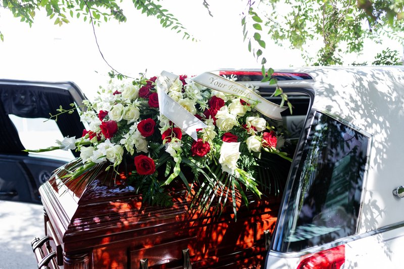 Beautiful red and white flowers on coffin in a hearse