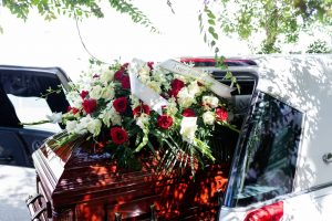 casket halfway out of a car with flowers on top