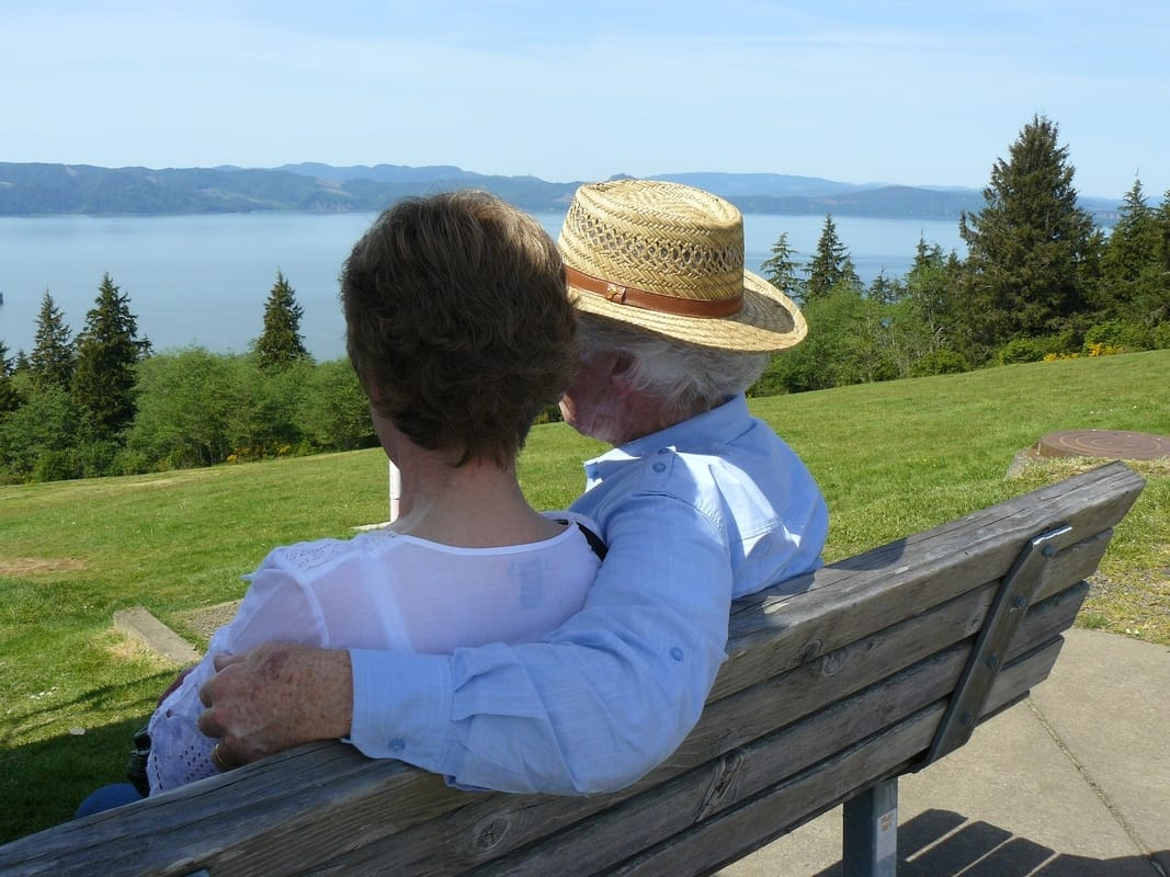 old couple sitting loving together on bench by lake