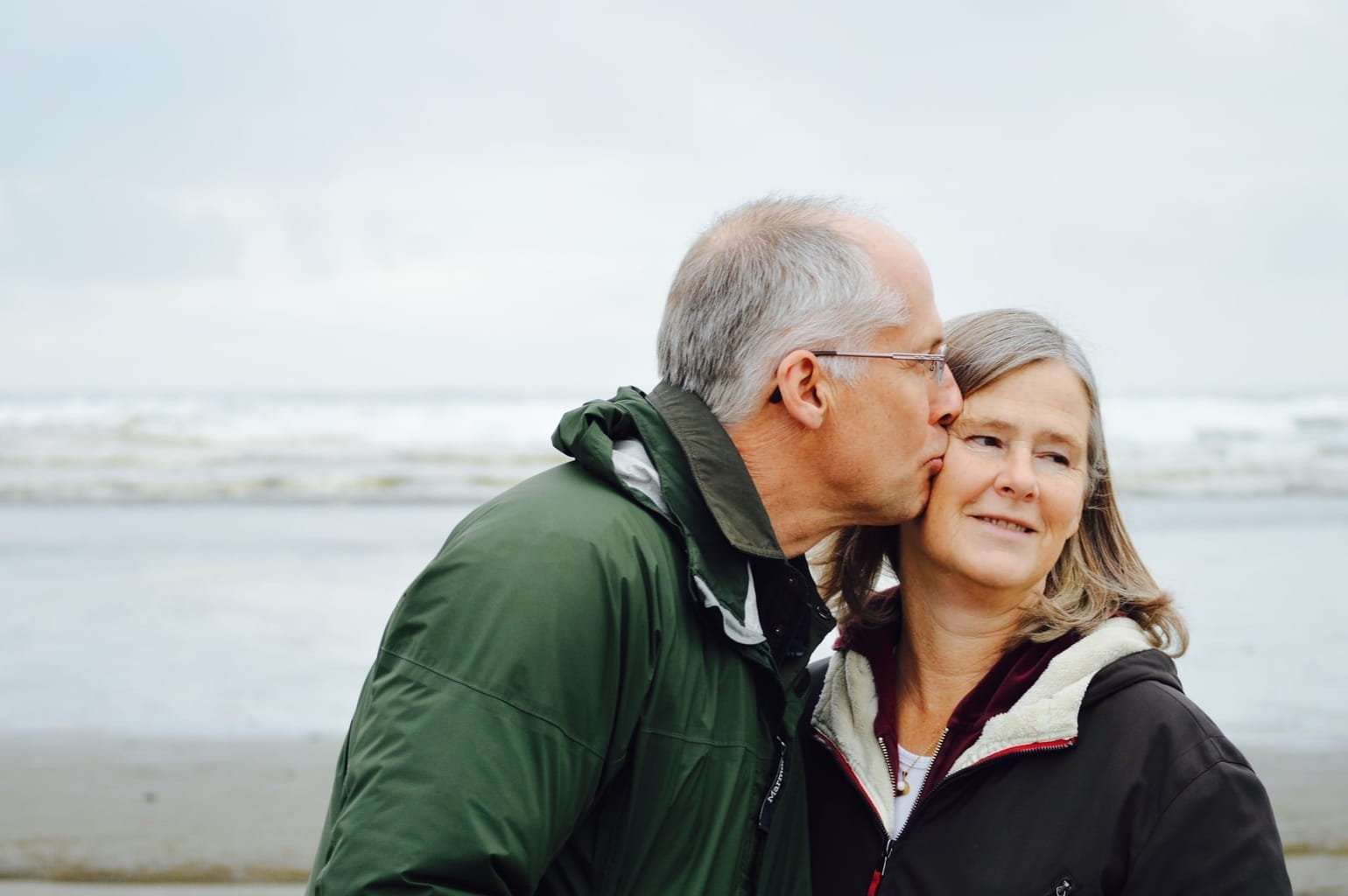 older man kissing wife on her cheek