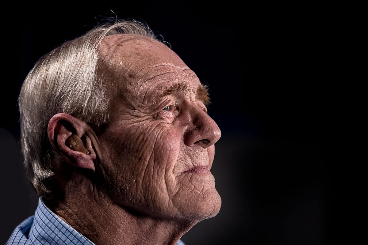 elderly man with hearing aid looking out in-front of him