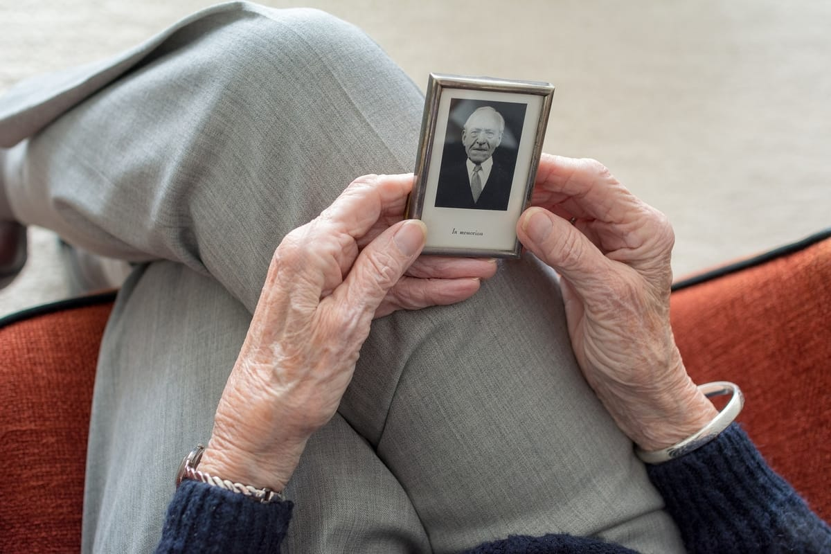 elderly woman holding a small picture of a man in her hands