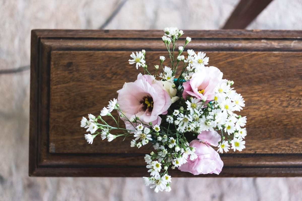 pink and white flower bouquet on top of coffin
