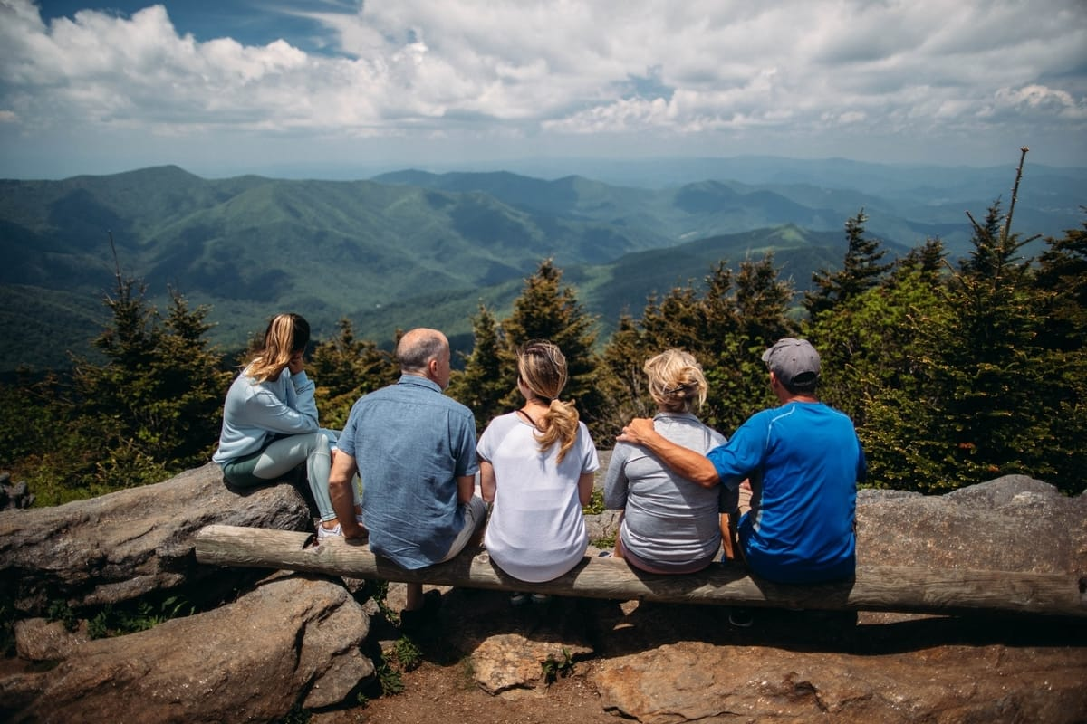 group of people sitting together overlooking the mountain