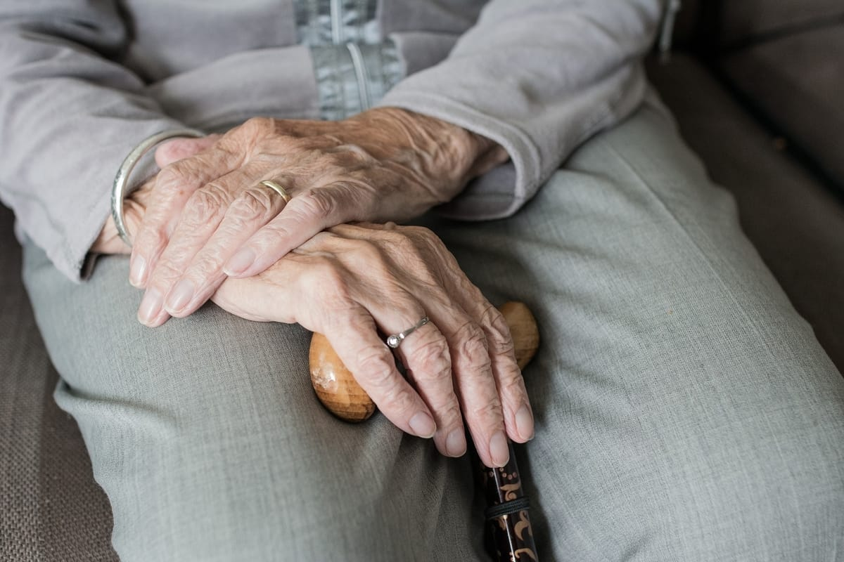 old person crossing hands and holding walking stick
