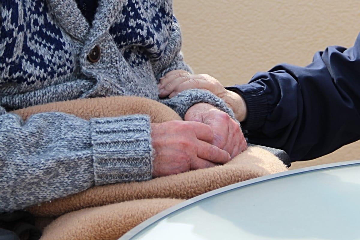 human nurturing older man by holding hands