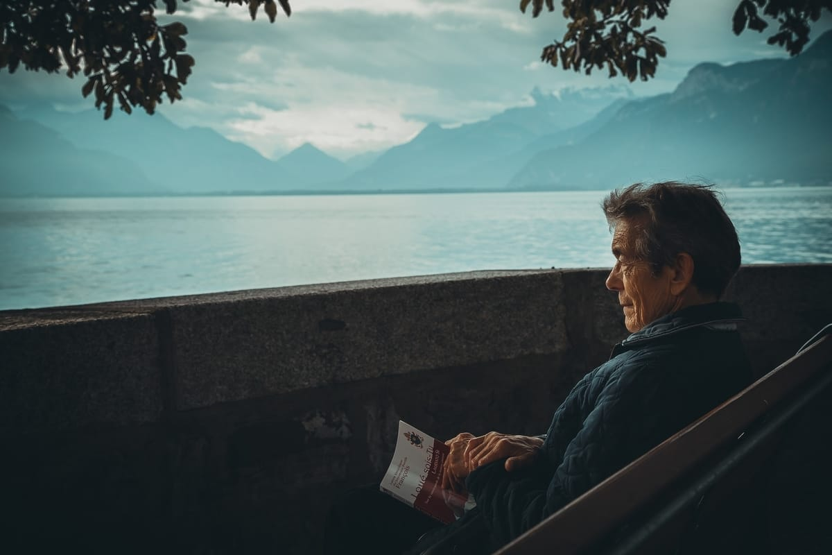 man alone reading book on bench