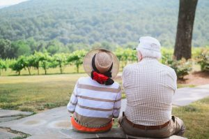 senior couple sitting on bench looking at mountains