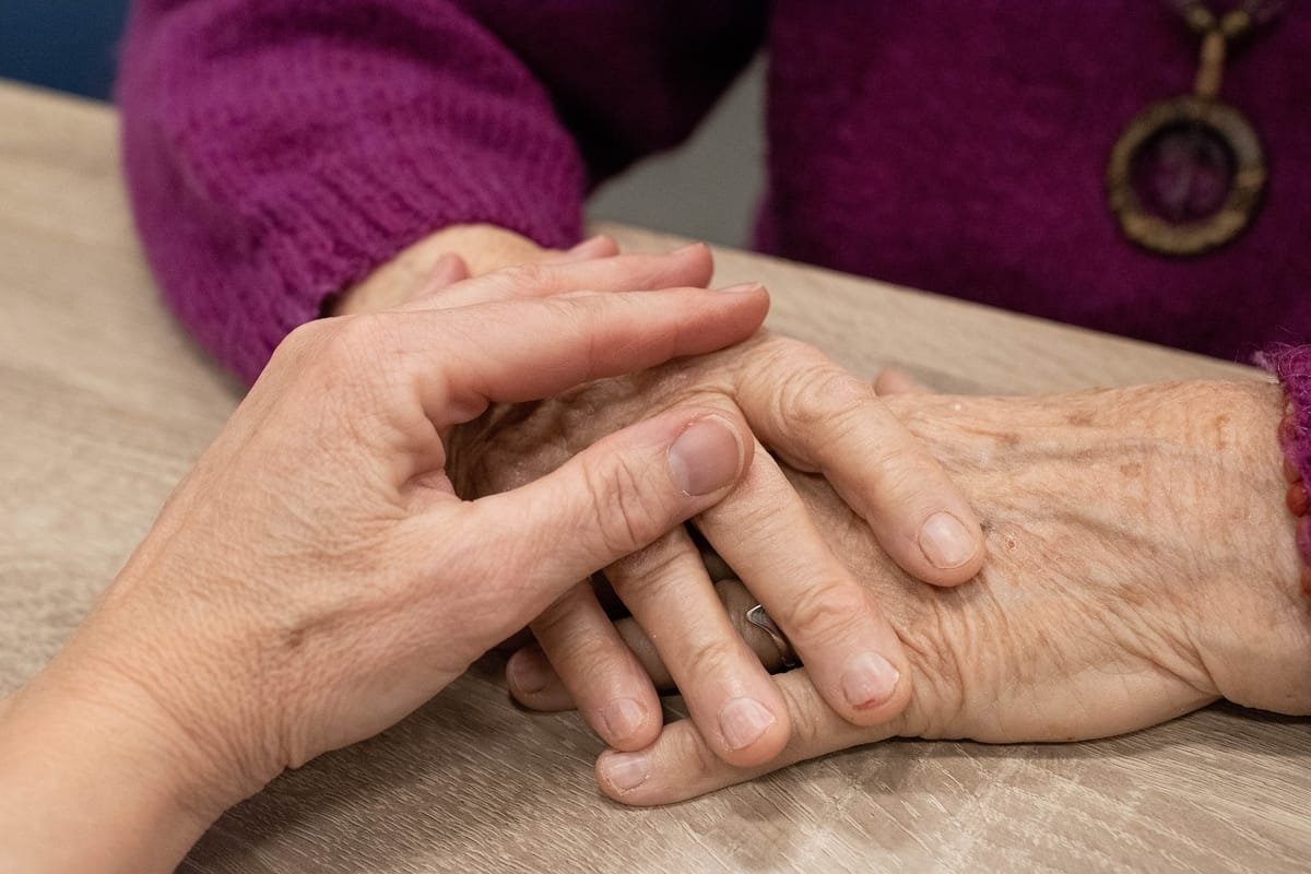 woman holding older womans hands