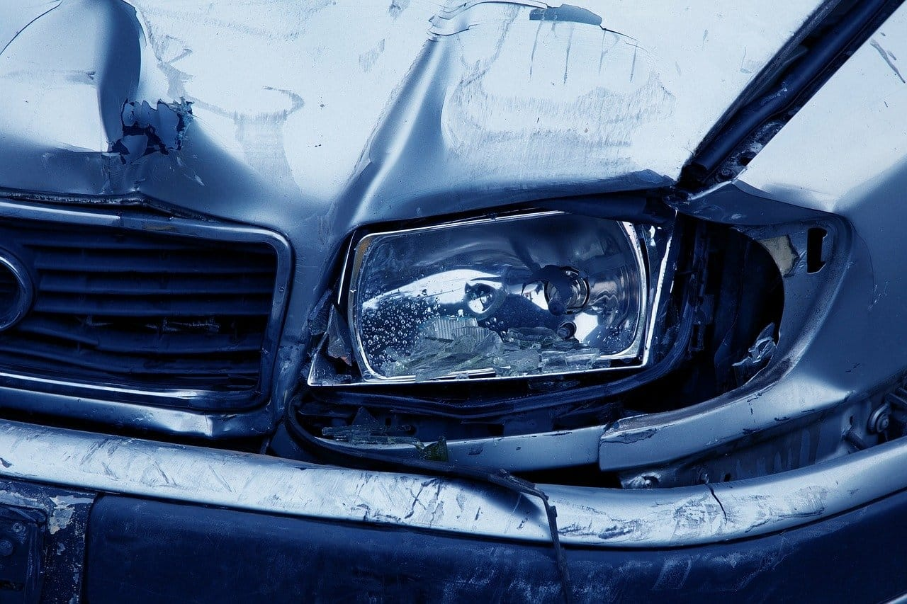 Close-up of a car with damage to the headlight and front of the vehicle