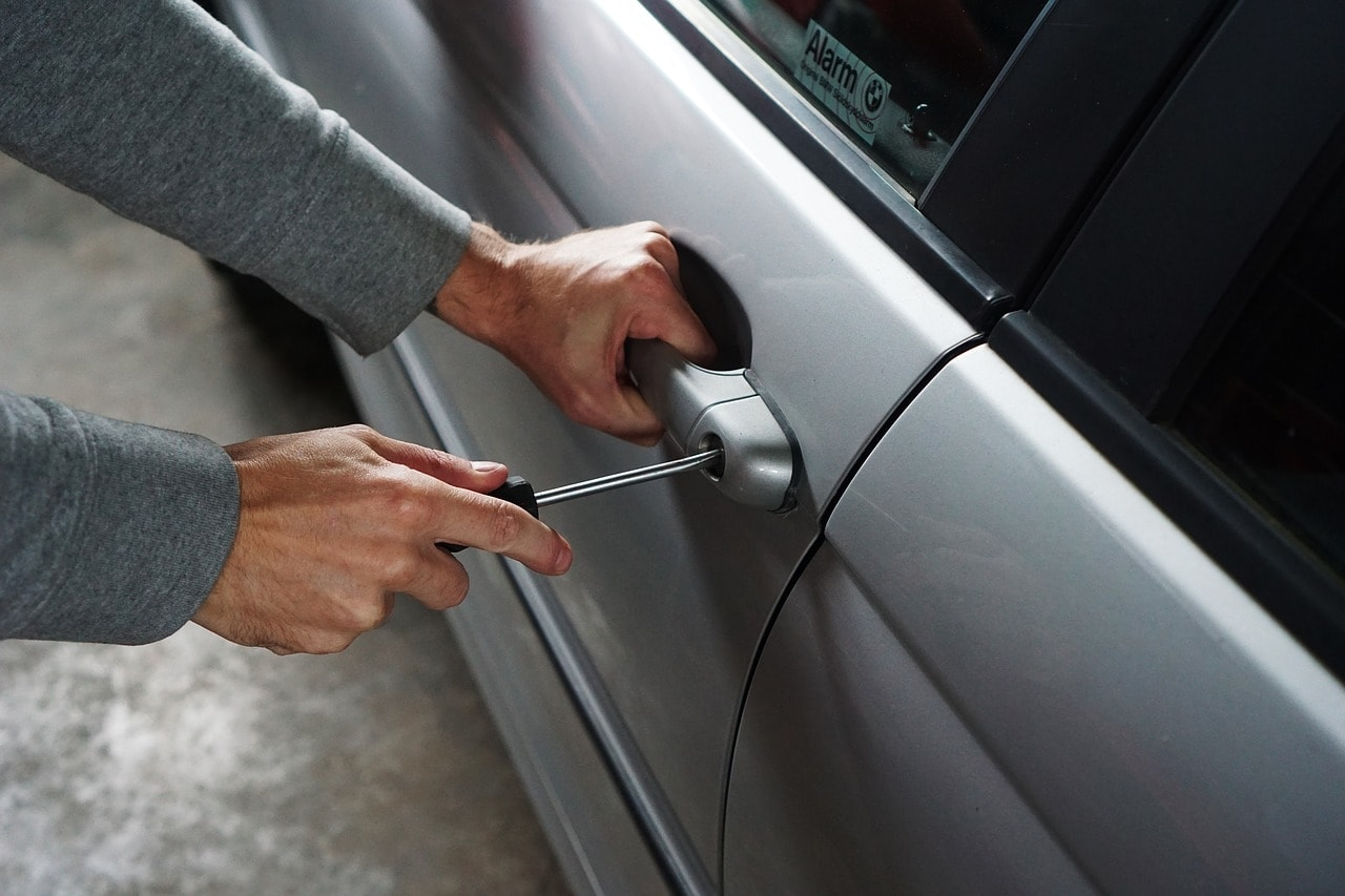 Man with a screwdriver attempting to break into a car via the driver's door