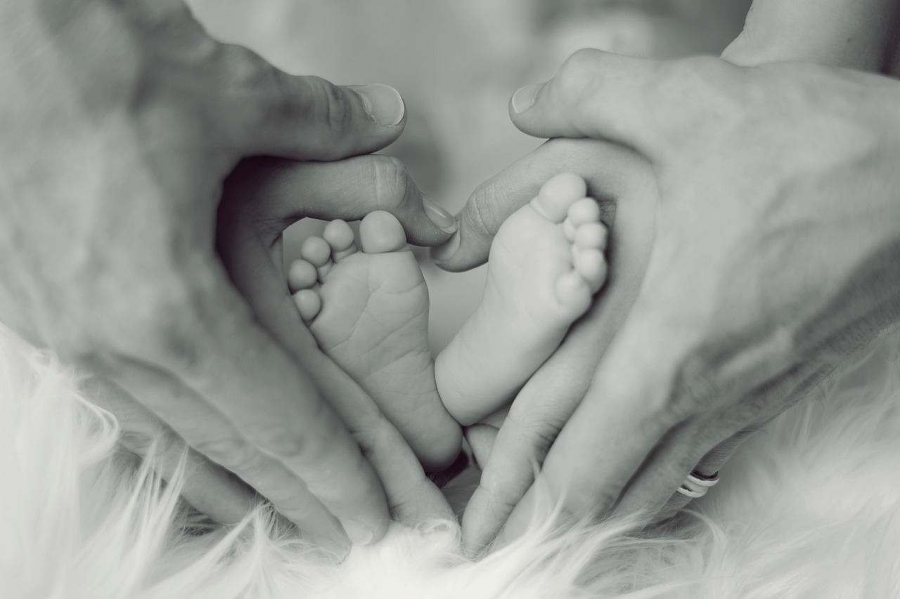 Parents' hands holding baby feet in a heart shape