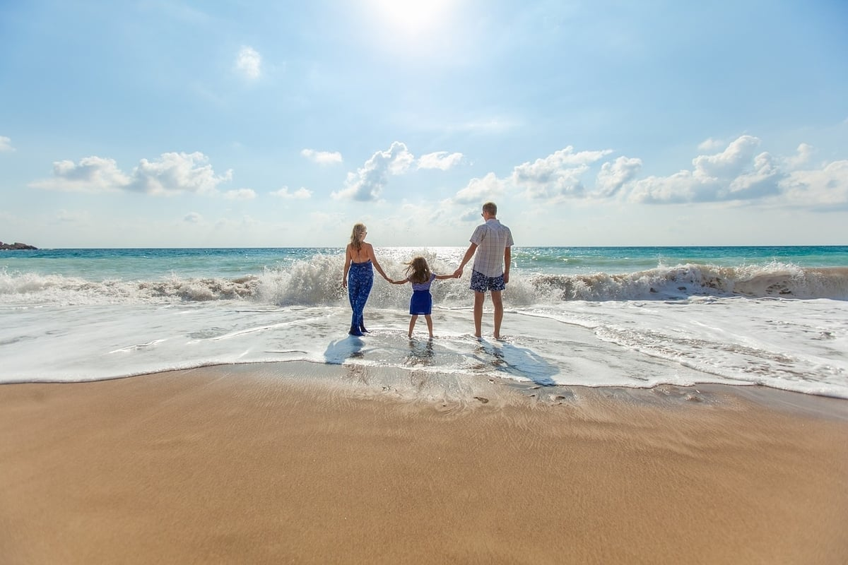 Parents with their child holding hands on a sandy beach