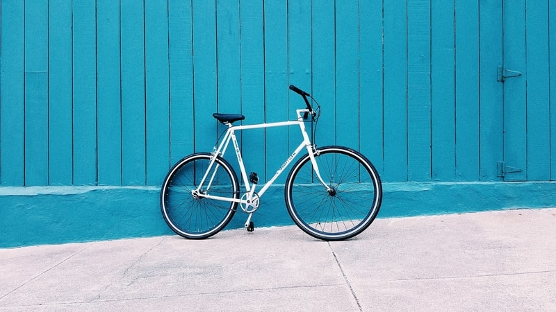 A white and black wheel bicycle leaning against a bright blue wall