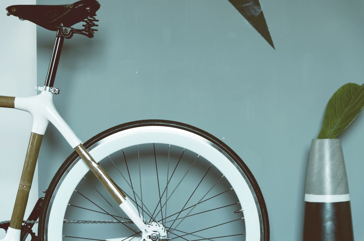 The back wheel of a white bicycle posted against a dolphin blue wall next to a vase and plant