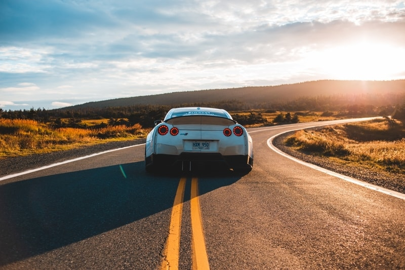 A sportscar driving along a deserted road into the sunset