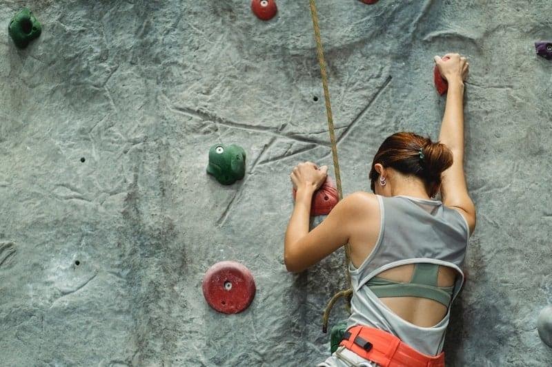 Woman climbing a rock climbing wall